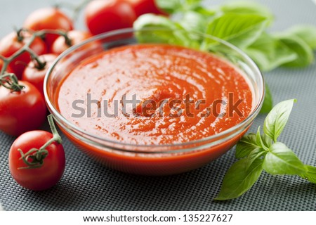 bowl of tomato pulp, pure, sauce, basil leaves - stock photo