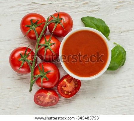 Bowl of tomato sauce with fresh ingredients  - stock photo