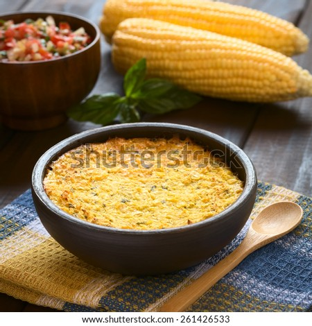 Bowl of traditional Chilean Pastel de Choclo (corn pie) photographed with natural light. Below the corn-basil mix is ground meat and other ingredients (Selective Focus, Focus one third into the dish)  - stock photo