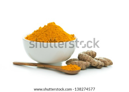 Bowl of turmeric powder with fresh turmeric root - stock photo