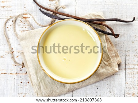 bowl of vanilla sauce on white wooden table, top view - stock photo