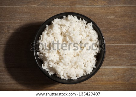 Bowl of white rice on wood grain background. - stock photo