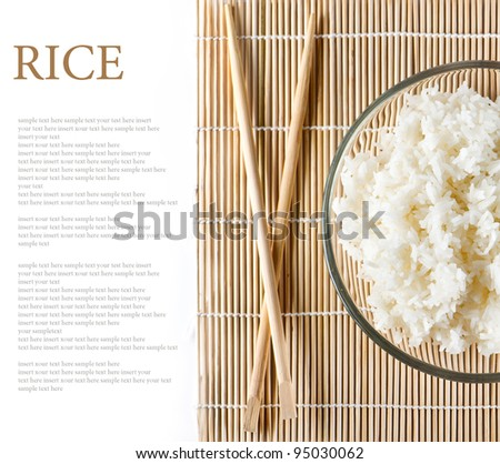 bowl of white steamed rice with chopsticks on bamboo mat. with place for your sample text - stock photo