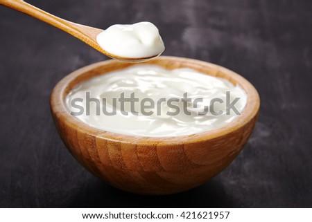bowl of white yoghurt over dark background - stock photo