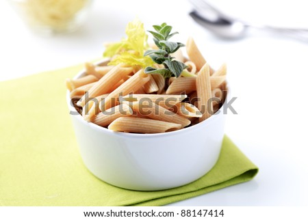 Bowl of whole wheat pasta tubes - closeup - stock photo