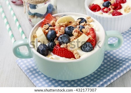 Bowl of yogurt with muesli and fresh fruits: strawberries, blueberries and bananas. - stock photo