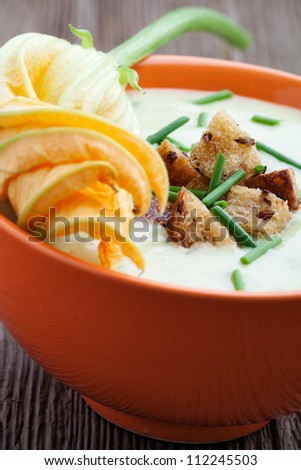 Bowl of zucchini soup with croutons and chives - stock photo