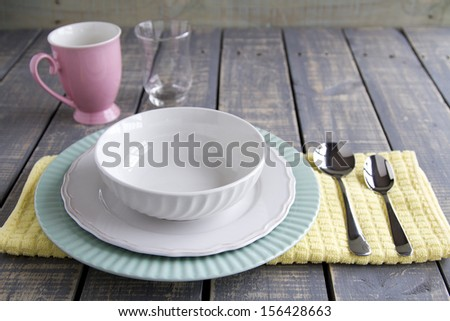 Bowl, plates and spoons on a cloth with glass and mug on wood table - stock photo