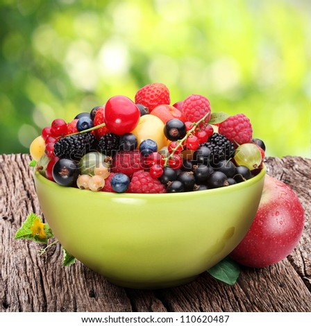 Bowl with a variety of berries on the old wooden table. Against the backdrop of summer foliage. - stock photo