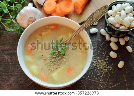 Bowl with bean soup and herbs - stock photo