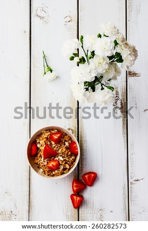 Bowl with cereals and fresh berries for healthy breakfast on white wooden table. Top view. - stock photo