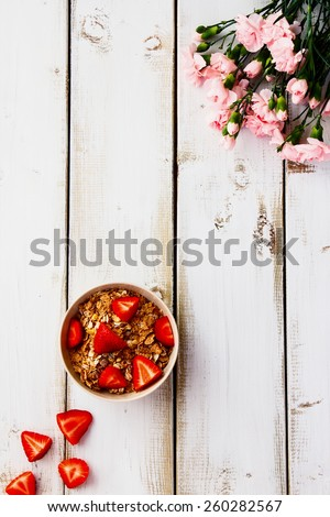Bowl with cereals and strawberries for breakfast on white wooden table. Top view. - stock photo