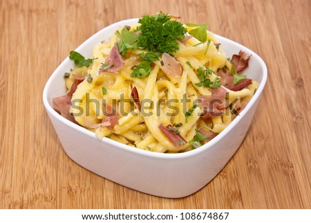 Bowl with Cheese Spaetzle on wooden background (decorated with Parsley) - stock photo