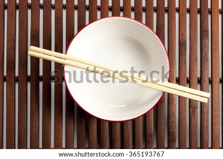 bowl with chopsticks on a bamboo mat - stock photo