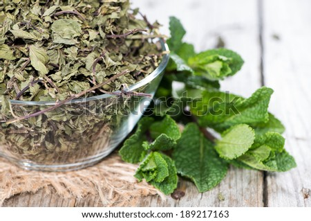 Bowl with dried Mint on vintage wooden background - stock photo