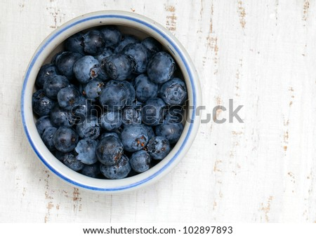bowl with fresh blueberries on wooden table - stock photo