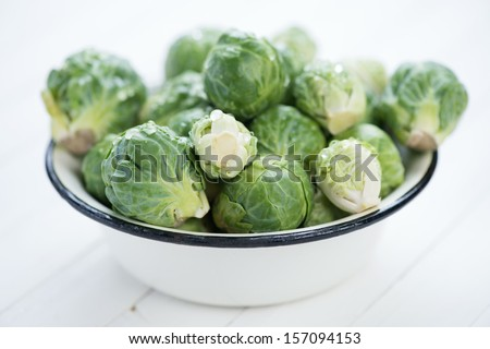 Bowl with fresh brussels sprouts on white wooden boards - stock photo