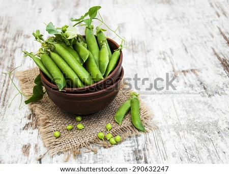 Bowl with fresh peas on a old wooden background - stock photo