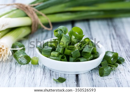 Bowl with fresh sliced Scallions (close-up shot) on wooden background - stock photo