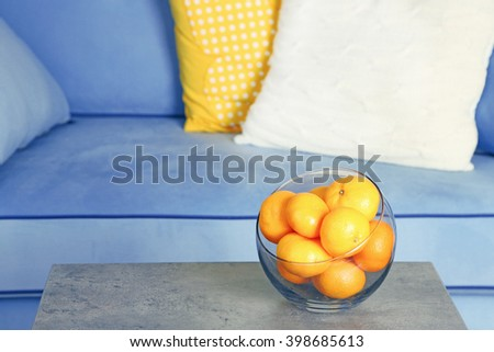 Bowl with fresh tangerines on table in living room, close up - stock photo