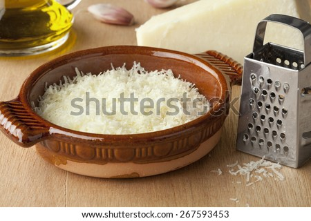 Bowl with grated Italian pecorino romano cheese, olive oil and garlic   - stock photo