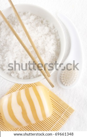 Bowl with natural salt of Dead Sea, bar of soap, brush and wooden sticks on white towel. - stock photo