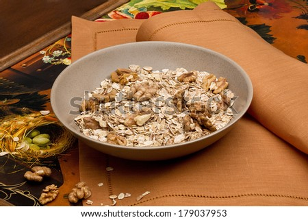 Bowl with nuts and muesli on table-napkin - stock photo
