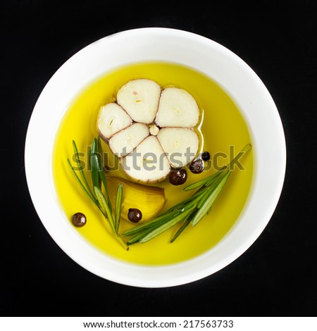 bowl with olive oil, garlic, peppercorn  and rosemary on a black background, top view, square image - stock photo