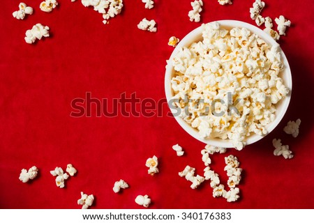 bowl with popcorn on red background. mock up. top view. - stock photo