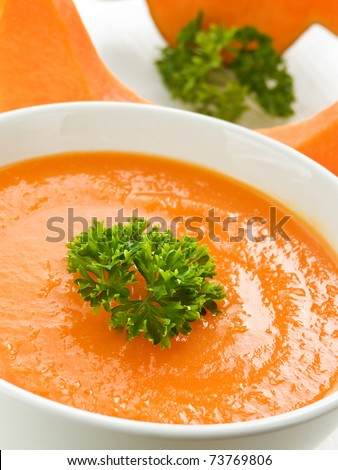 Bowl with pumpkin soup and parsley. Shallow dof. - stock photo