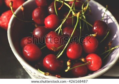 Bowl with red ripe cherries macro photo. Close up photo of cherry ceramic bowl on the table in sunny room. - stock photo