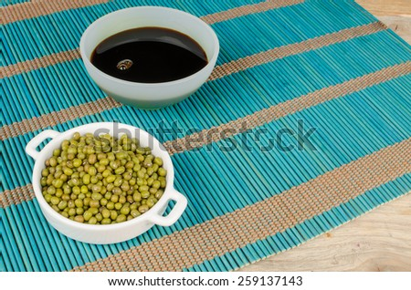 Bowl with soy sauce and soy beans on a bamboo mat - stock photo