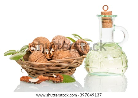 Bowl with walnuts and oil bottle isolated on white background. - stock photo