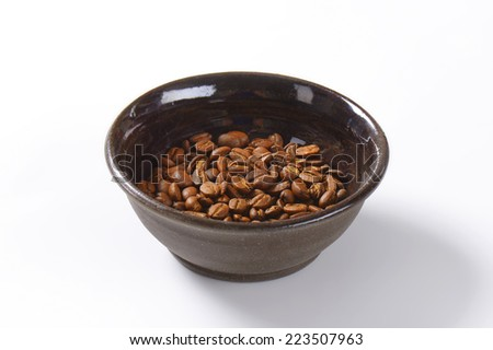 bowl with whole roasted coffee seeds - stock photo