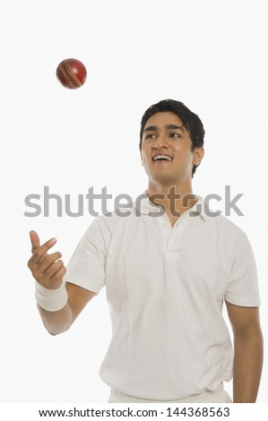 Bowler tossing a cricket ball - stock photo
