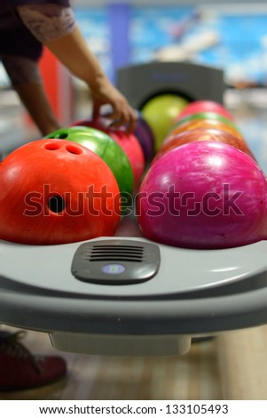 Bowling ball machine with person taking ball in the background - stock photo
