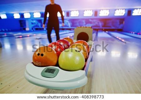 Bowling balls at bowl lift with ultraviolet lighting - stock photo