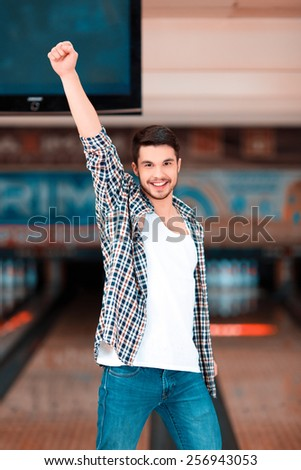 Bowling master. Cheerful young man raising his hands high above the head and smiling at camera while standing against bowling alleys after the strike - stock photo
