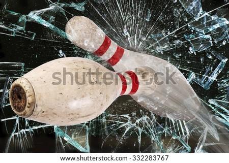 Bowling pin shattering a glass window. - stock photo