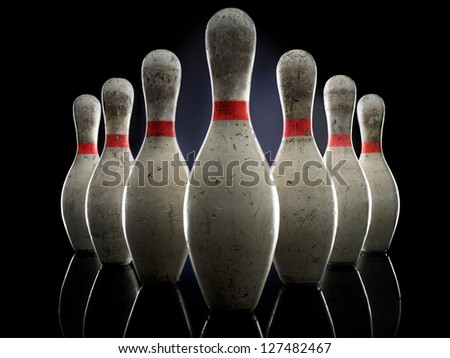 Bowling pins illuminated over black background - stock photo