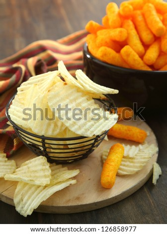 Bowls filled with Potato chips  and Cheese sticks - stock photo
