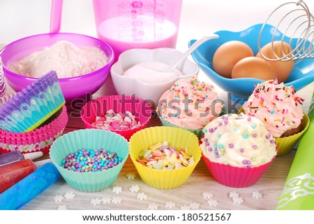 bowls of ingredients needed for baking colorful cupcakes   - stock photo