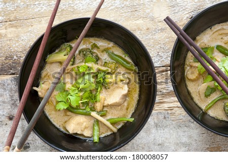 Bowls of tasty Thai green curry served with chopsticks made from nutritional bean sprouts, broccoli, chicken, coconut milk, coriander,and green beans, view from above - stock photo