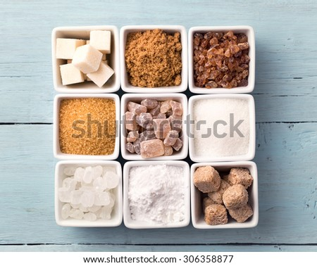 Bowls of various kinds of sugar on old blue background - stock photo