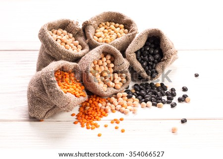Bowls of various legumes on wooden background,healthy food,vegan food. - stock photo