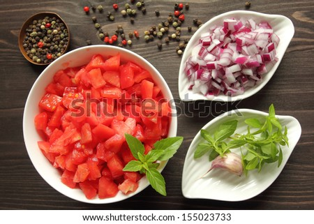 Bowls with chopped raw  tomatoes and onions on tomato sauce - stock photo