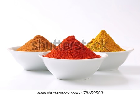 bowls with ground cinnamon, curry and red pepper - stock photo