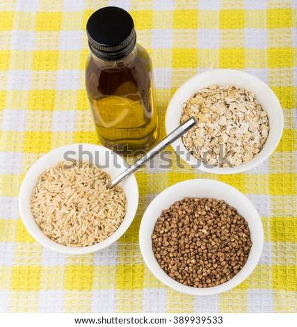 Bowls with oats, buckwheat, brown rice and bottle oil on yellow tablecloth - stock photo