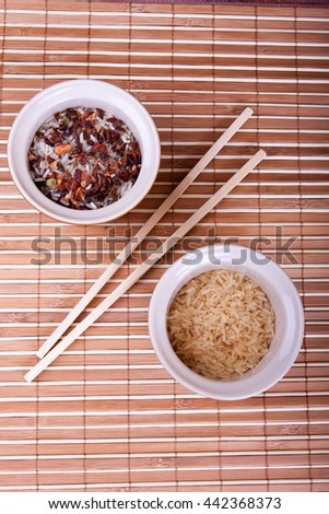 Bowls with raw rice and chopsticks on the bamboo tablecloth - stock photo