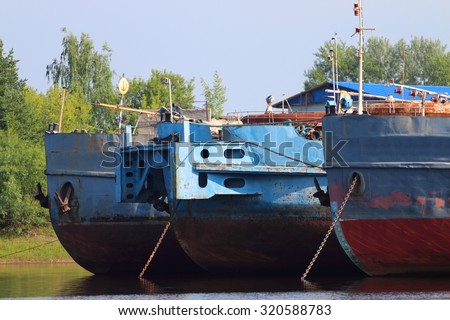 Bows of three rusty cargo ships and lowered anchors on river at summer day - stock photo